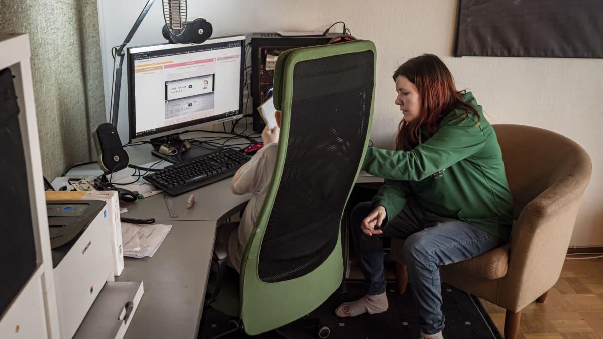 Susanna Holmquist opastaa lasta koulutehtävissä kotona