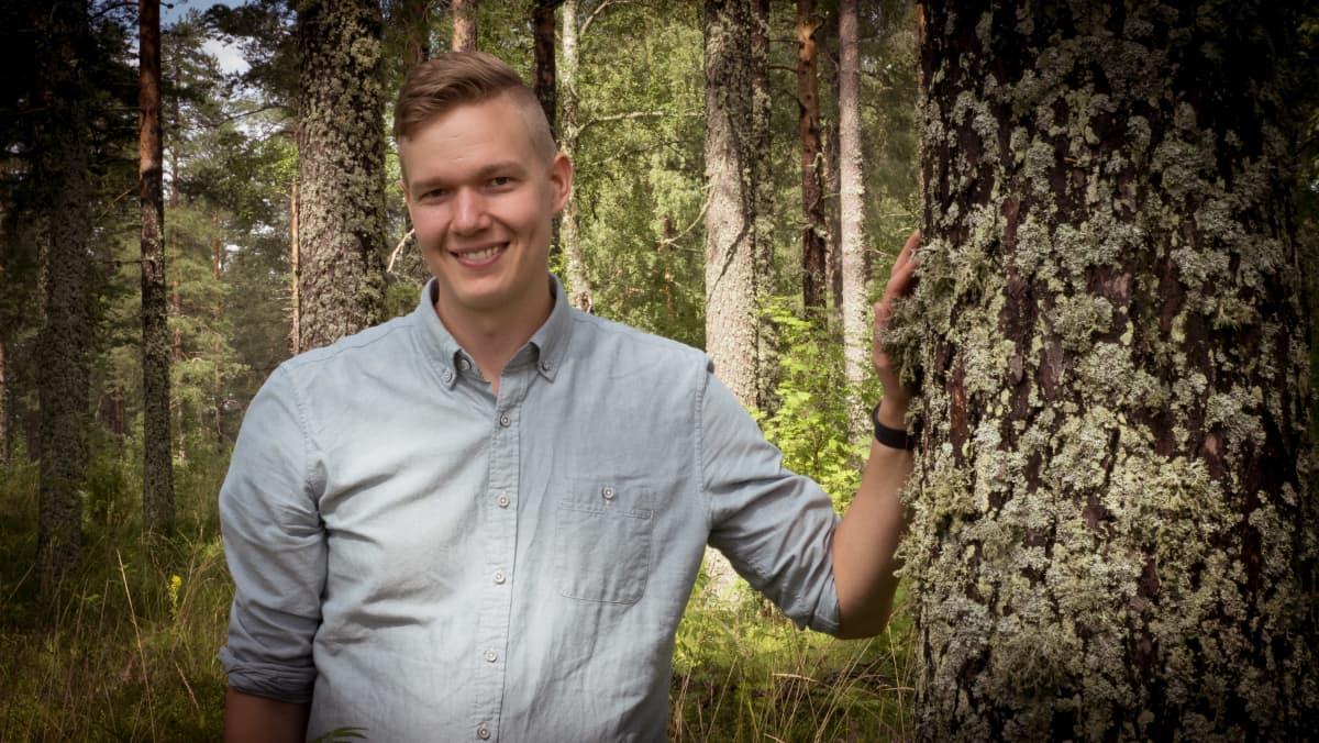 Mies nojaa metsässä kädellään mäntyyn