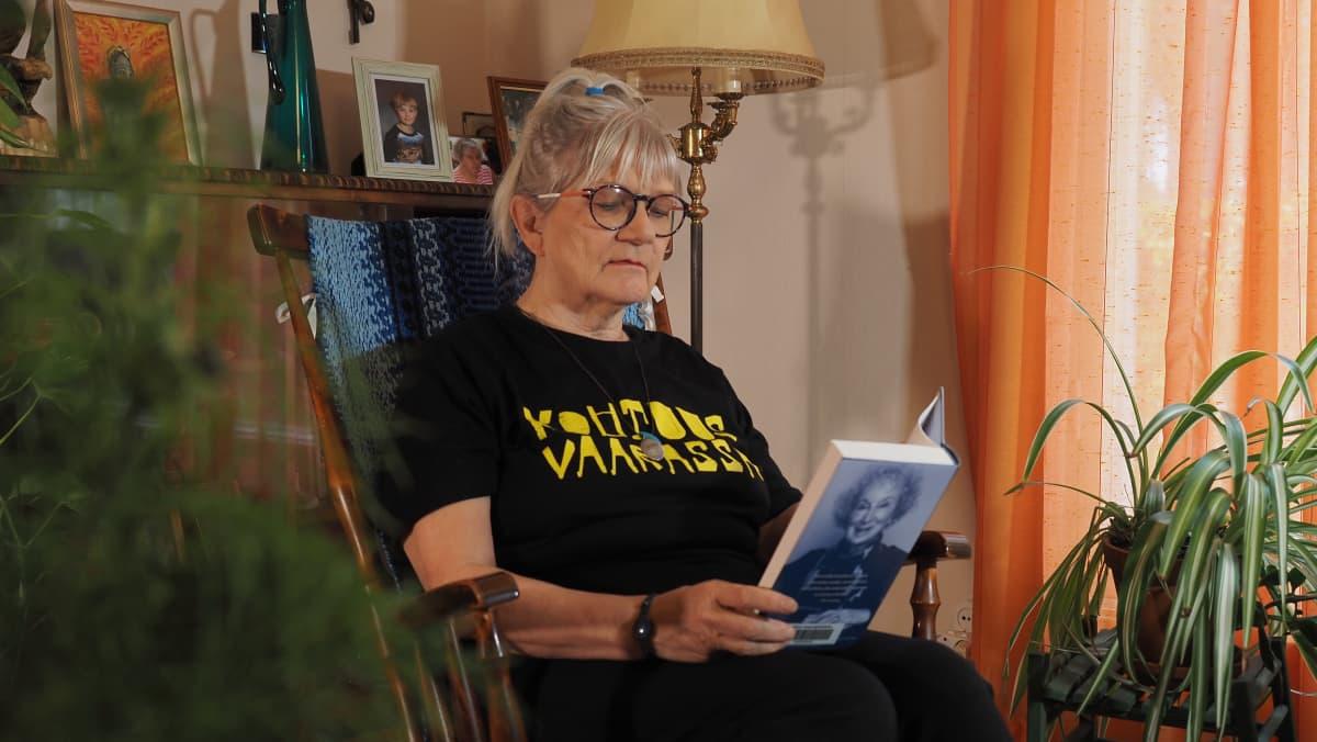 Kirjailija Ulla Vaarnamo lukee kirjaa kiikkutuolissa.