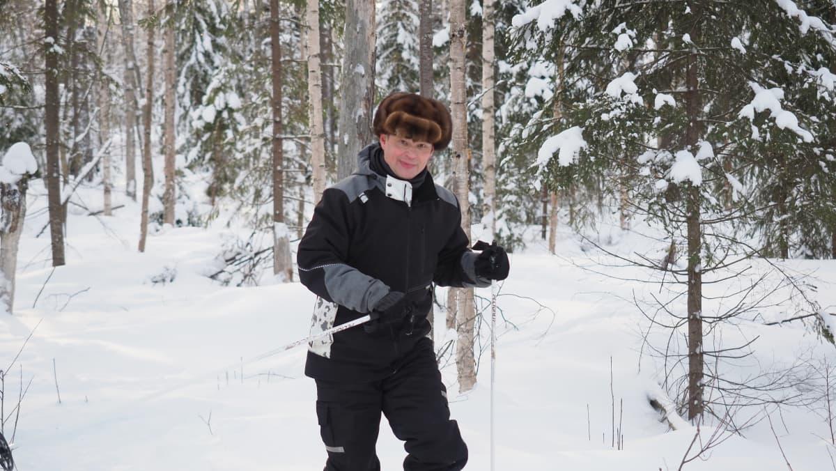 Ympäristöpäällikkö Antti Suontama hiihtää metsassä.