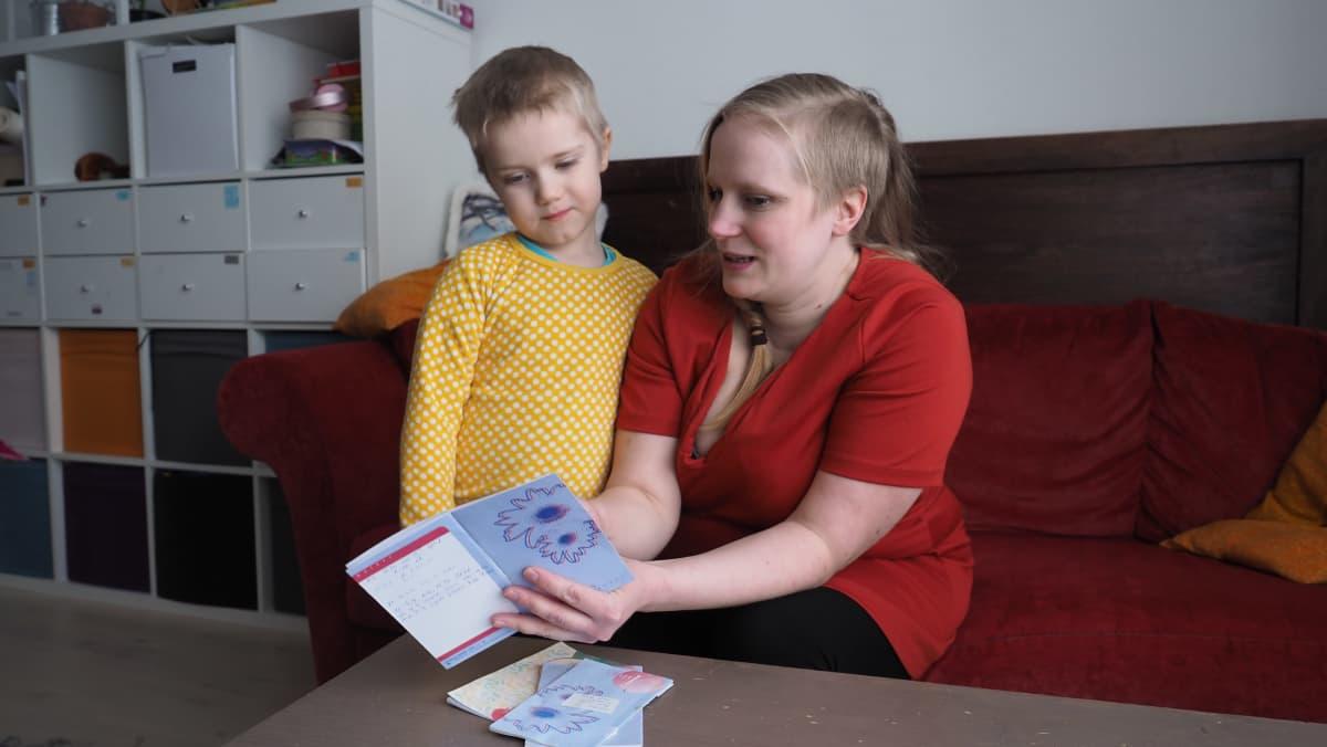 Äiti ja poika tutkivat äitiyskorttia.
