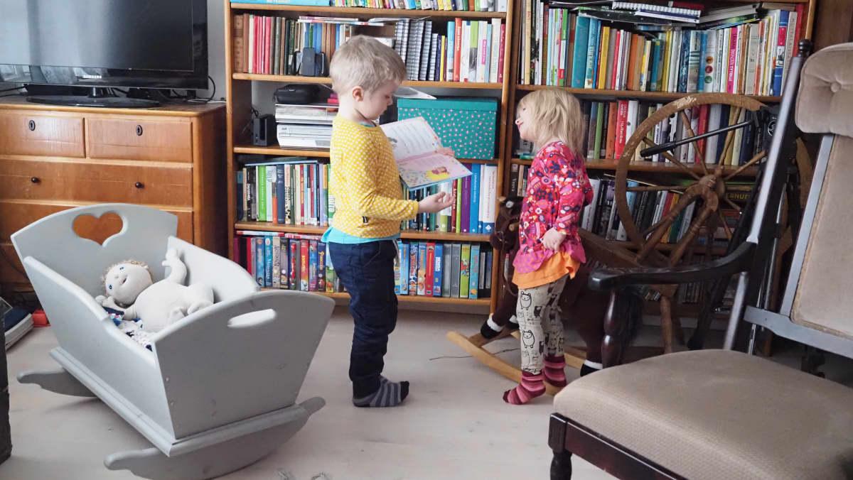 Tyttö ja poika seisovat kirjahyllyn edessä.