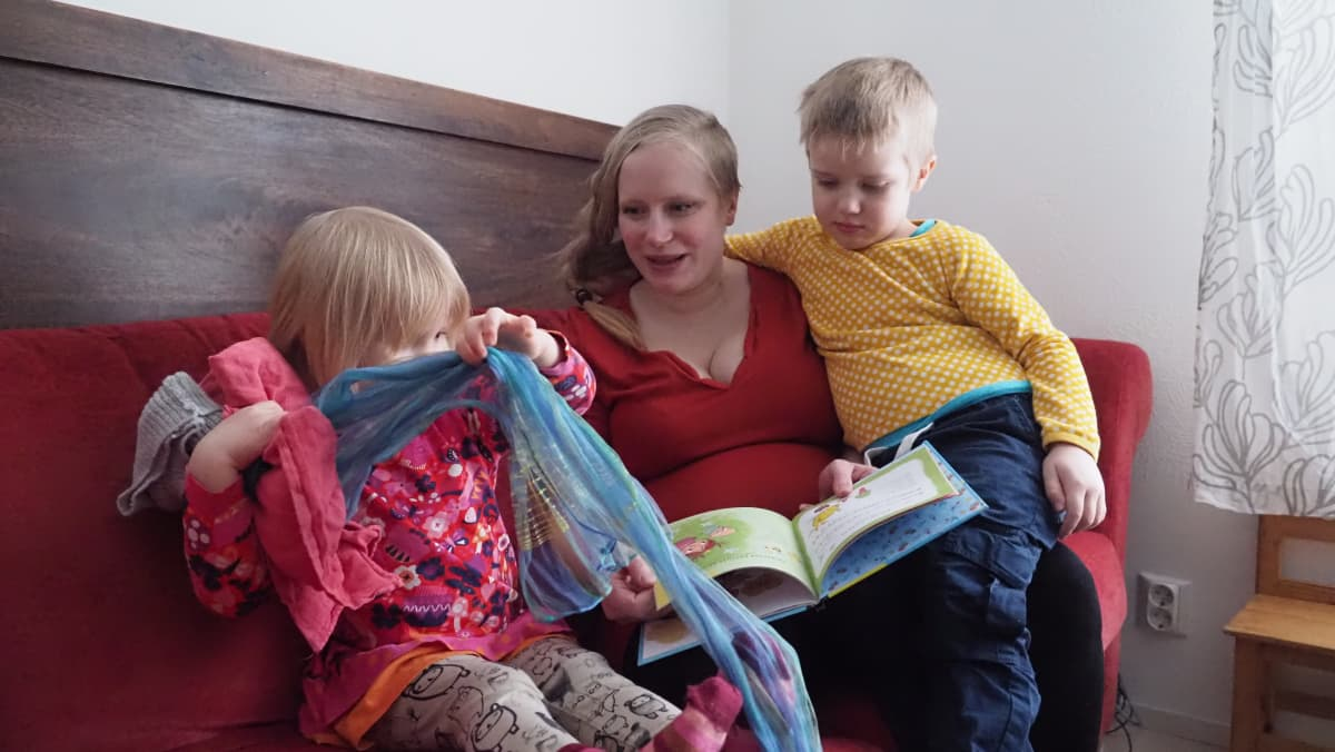 Jemina Virrantalo, tytär ja poika olohuoneen sohvalla.