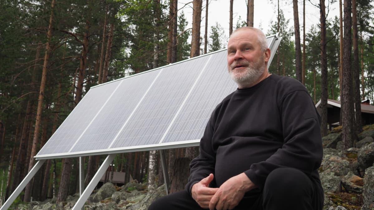 Kesämökkelijä Heikki Haaranen aurinkopaneeleidensa edessä, mökkisaarensa kivikkoisella rannalla.