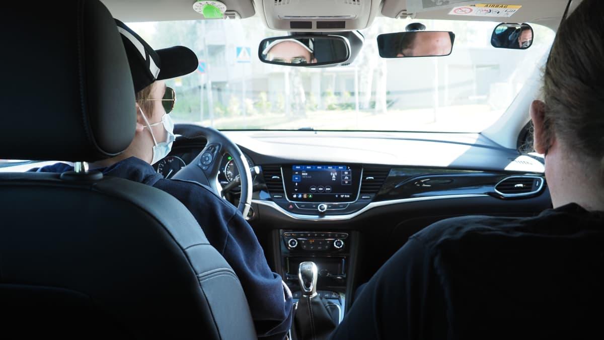 Oppilas ja opettaja ajotunnilla autossa.