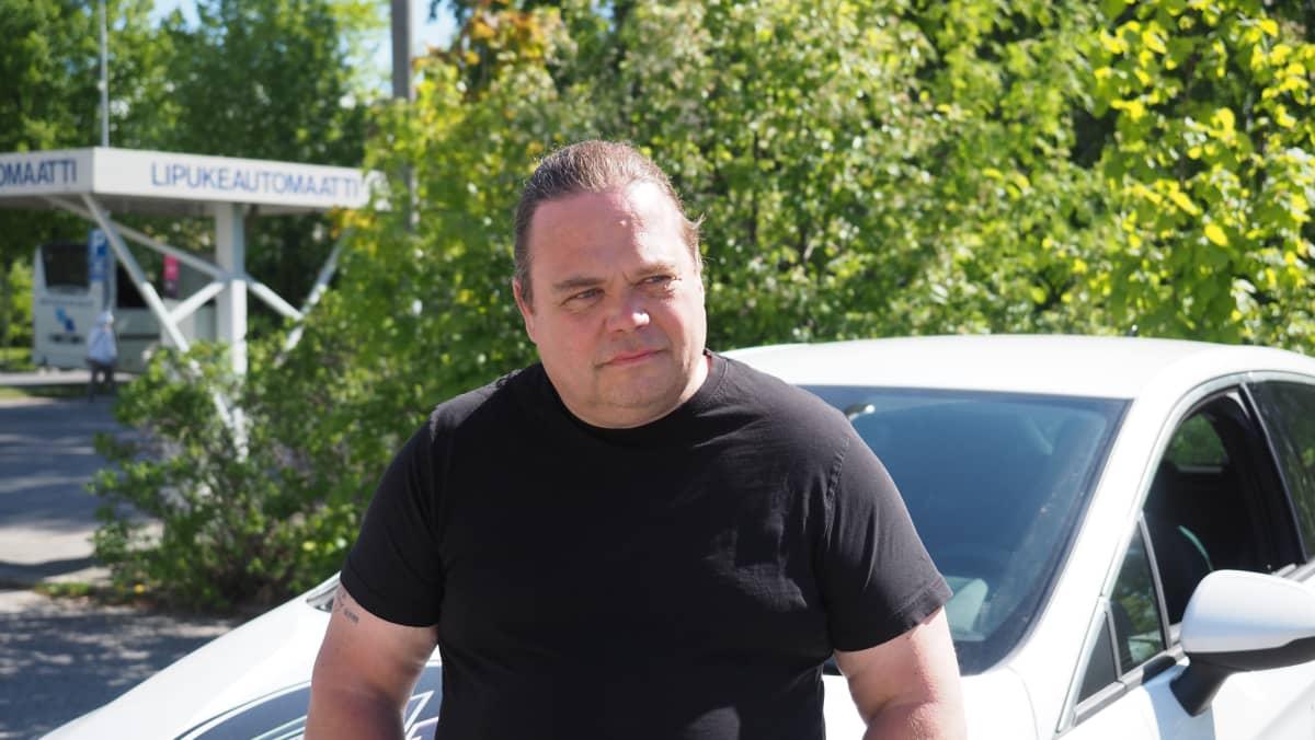 Liikenneopettaja Pekka Vartiainen nojaa autoon parkkipaikalla.