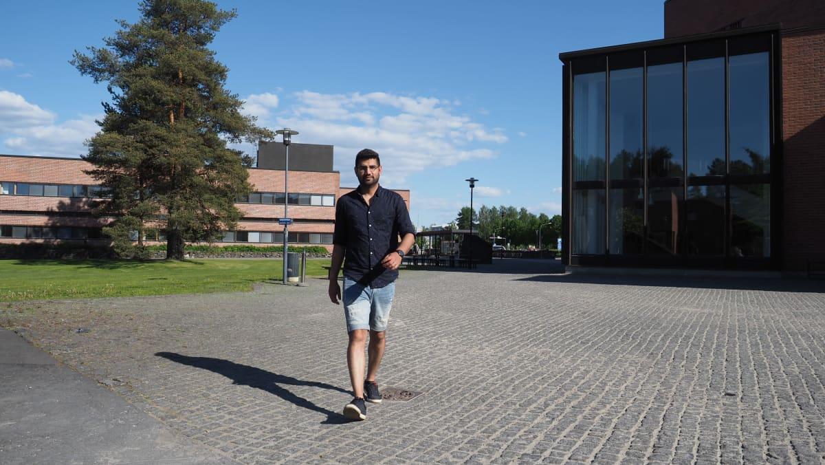 Wagar Zafar kävelee kohti yliopiston pihalla.