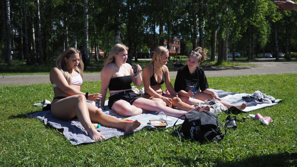Noora Salomies, Hanna Räty, Mona Hartikainen ja Kiia Voutilainen istuvat aurinkoisena päivänä uimarannalla ja juovat energiajuomaa.