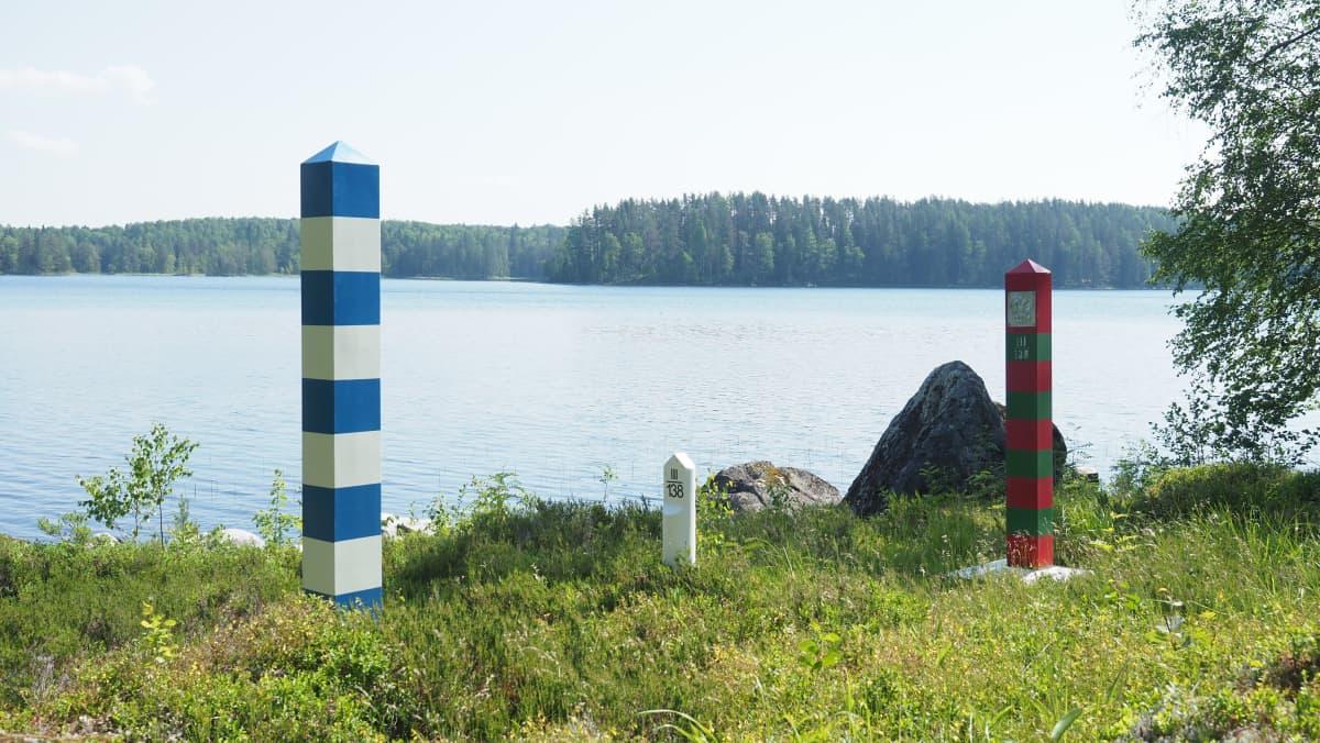 Suomen ja Venäjän rajamerkit vierekkäin maastossa järven rannalla.