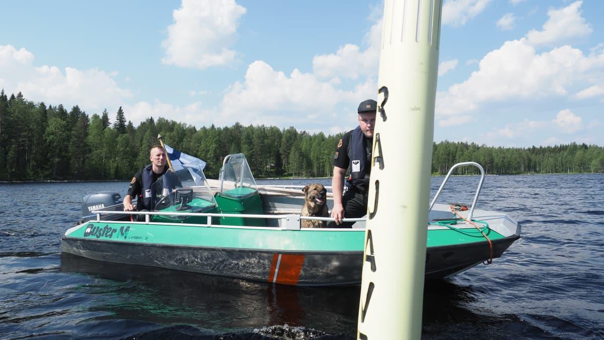 Rajamiehet ja koira tarkastavat veneellä rajapoijuja.