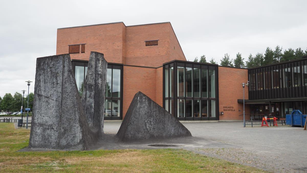 Edustalla Alkukivet-taideteos ja taustalla punatiilinen yliopistorakennus.