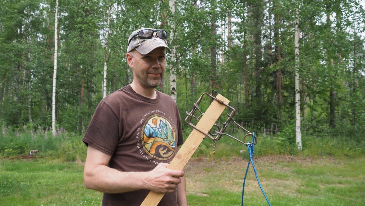 Riistasuunnittelija Kai-Eerik Nyholm pitelee puukapulassa kiinni olevaa pienpetopyydystä kädessään.