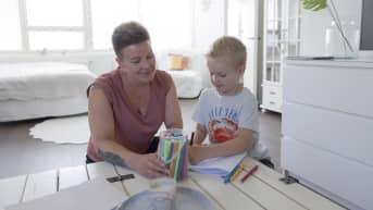 Äiti katsoo, kun lapsi piirtää.
