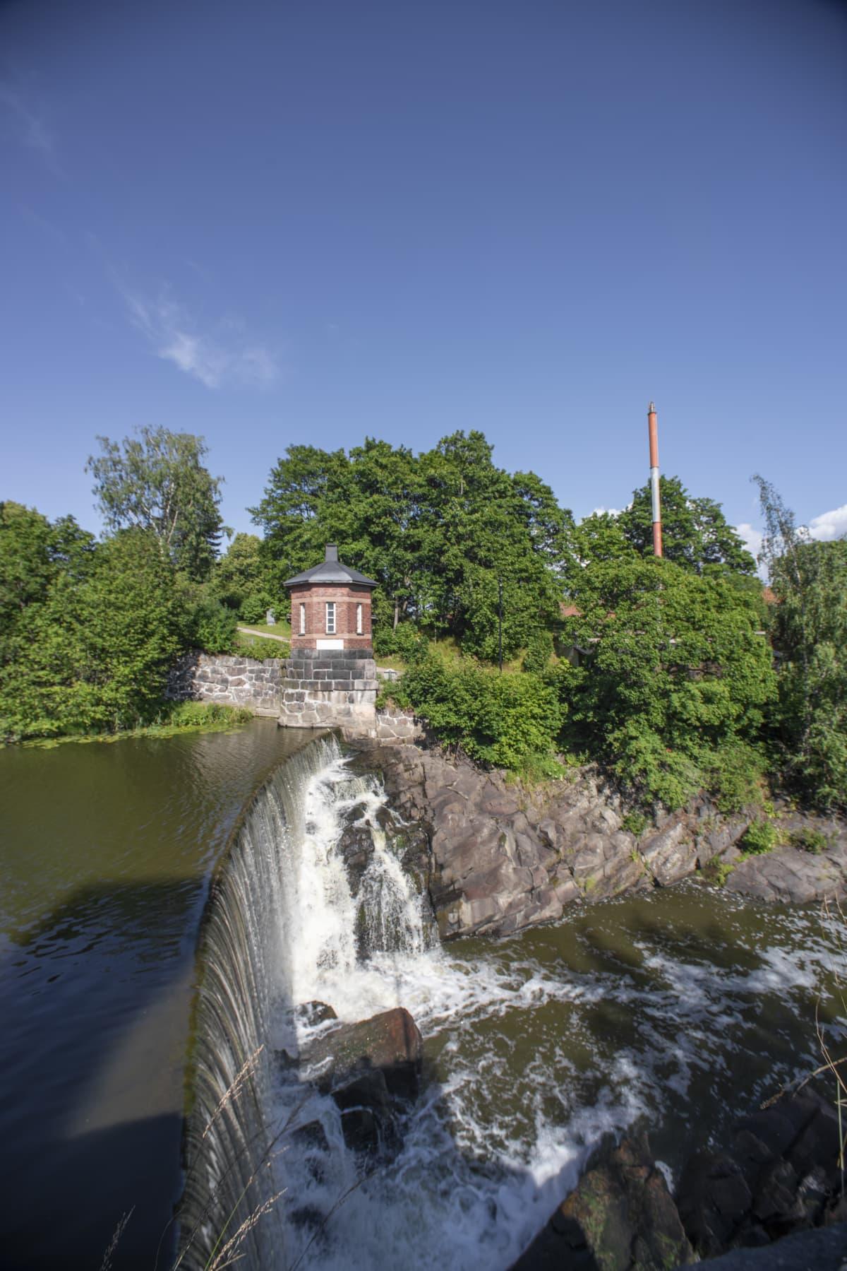 En damm som vattnet forsar över, ner i ett vattenfall. I bakgrunden syns träd och ett litet tegelhus. Det är en solig dag, himlen är blå.