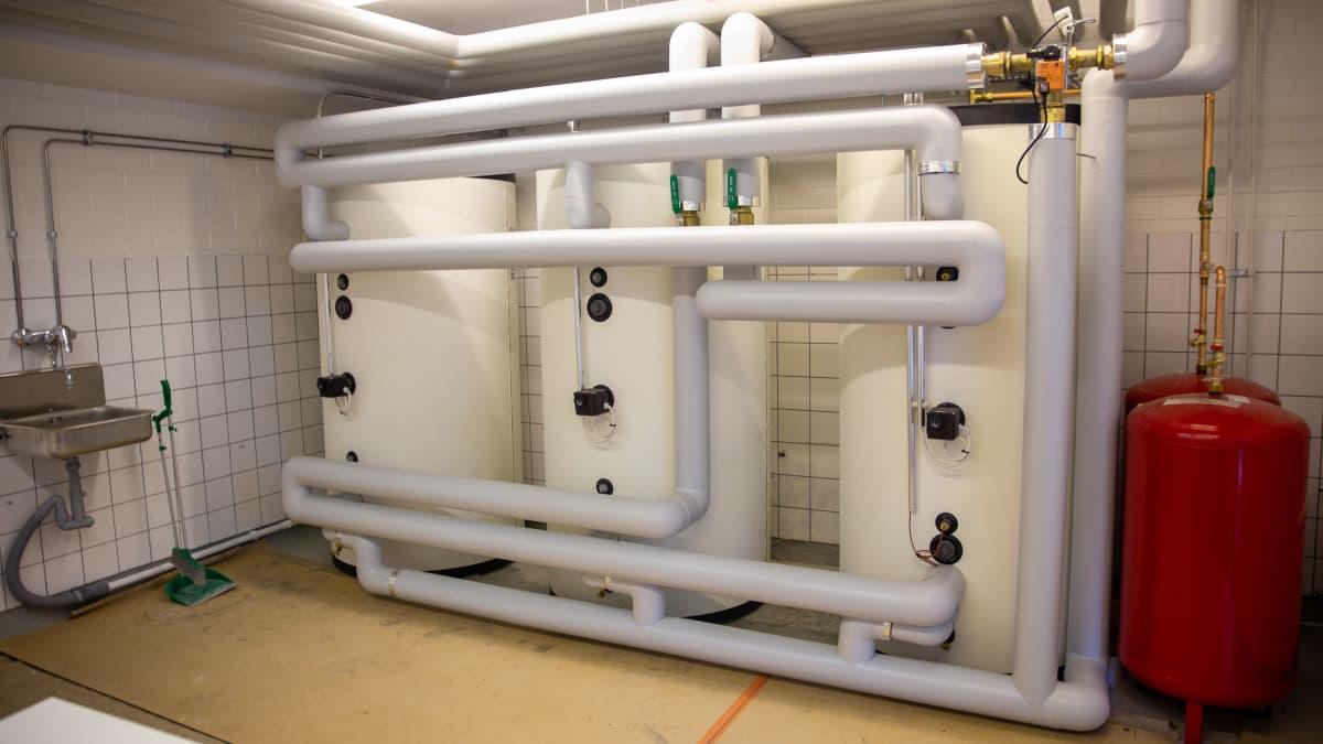 Maalämpöön liittyviä lämminvesivaraajia asennettuna taloyhtiön pesuhuoneeseen.
