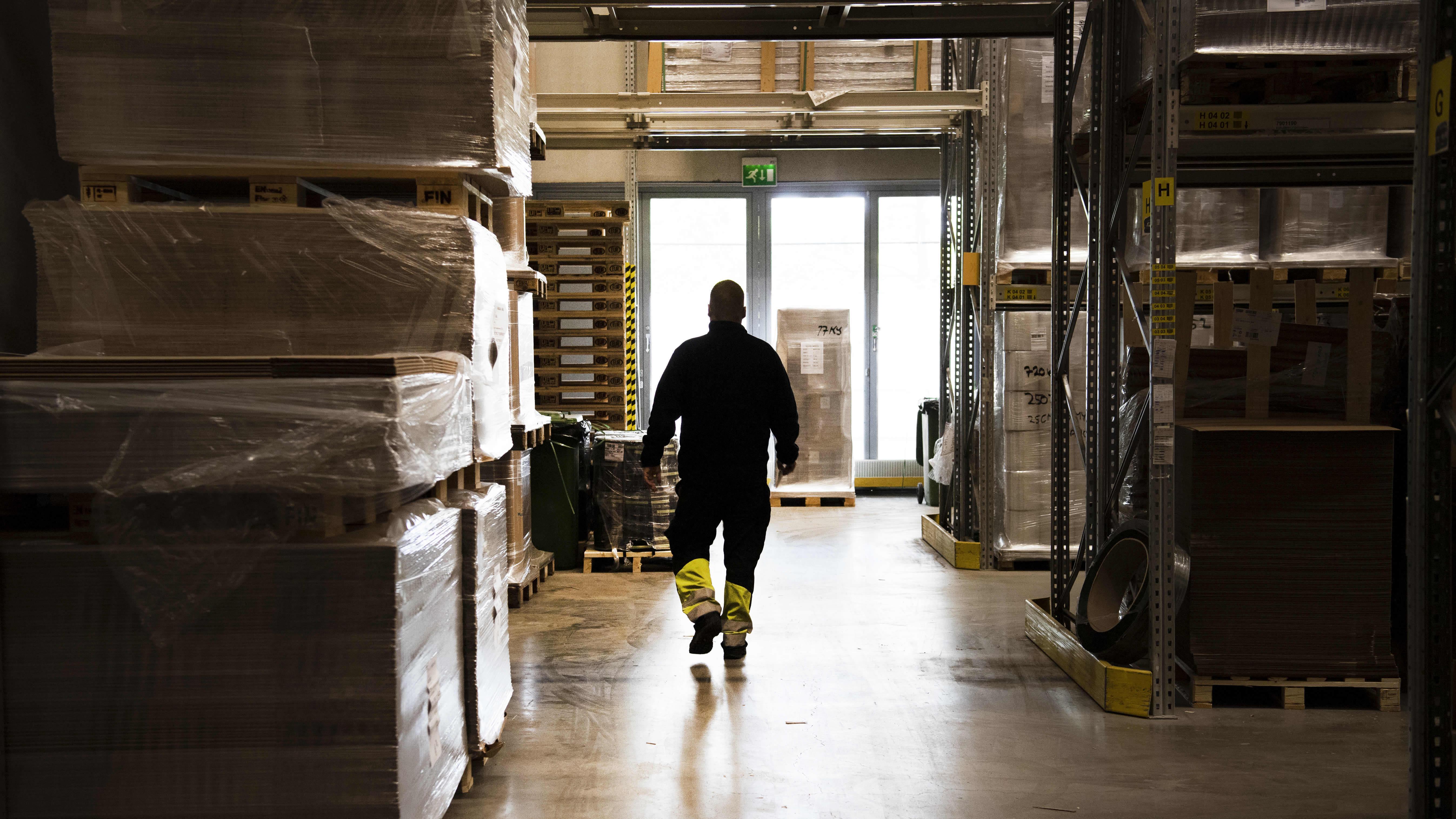 Työntekijä kävelee työpaikkansa varastossa.