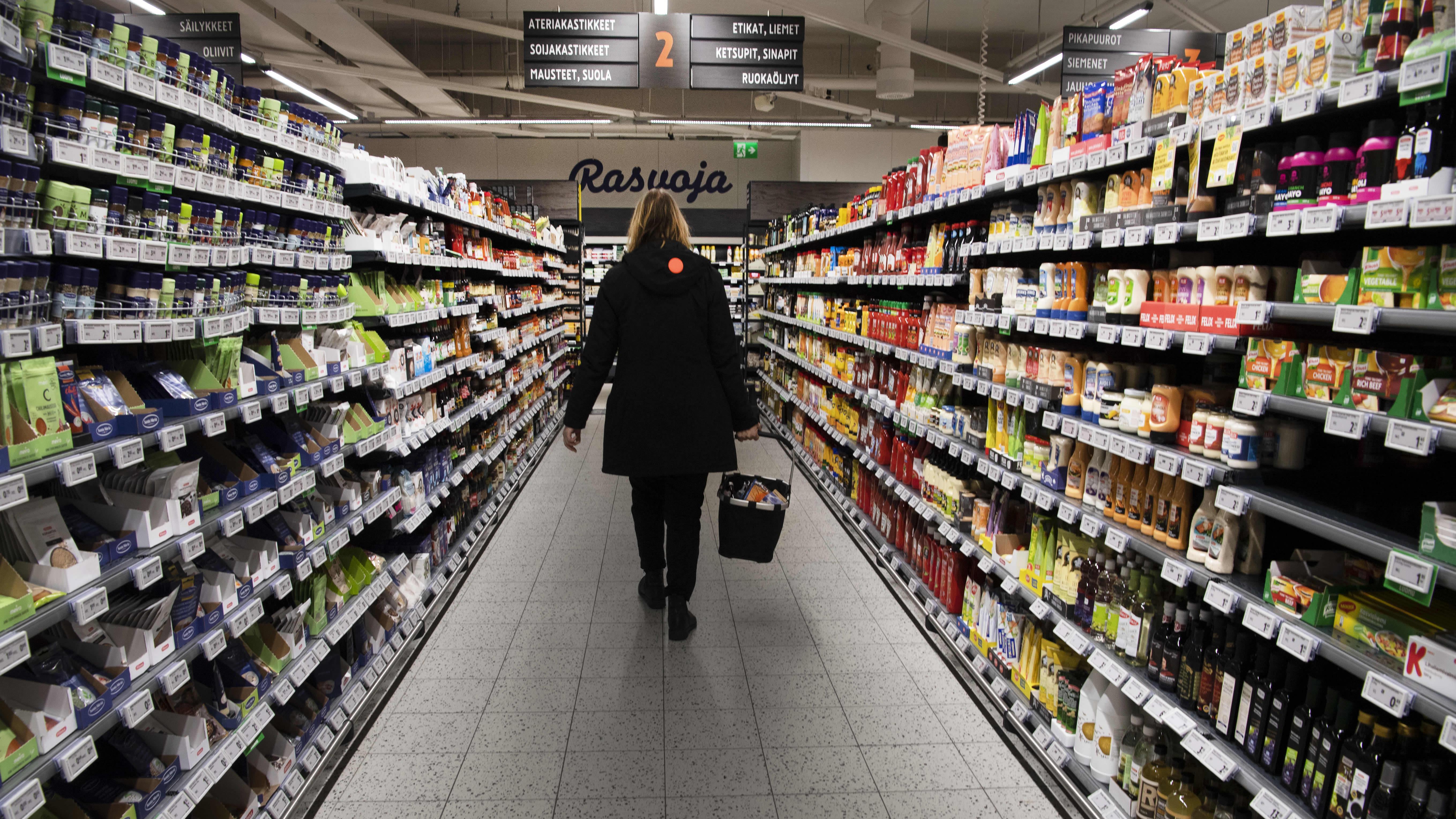 Asiakas kantaa ostoskoria ruokakaupassa.