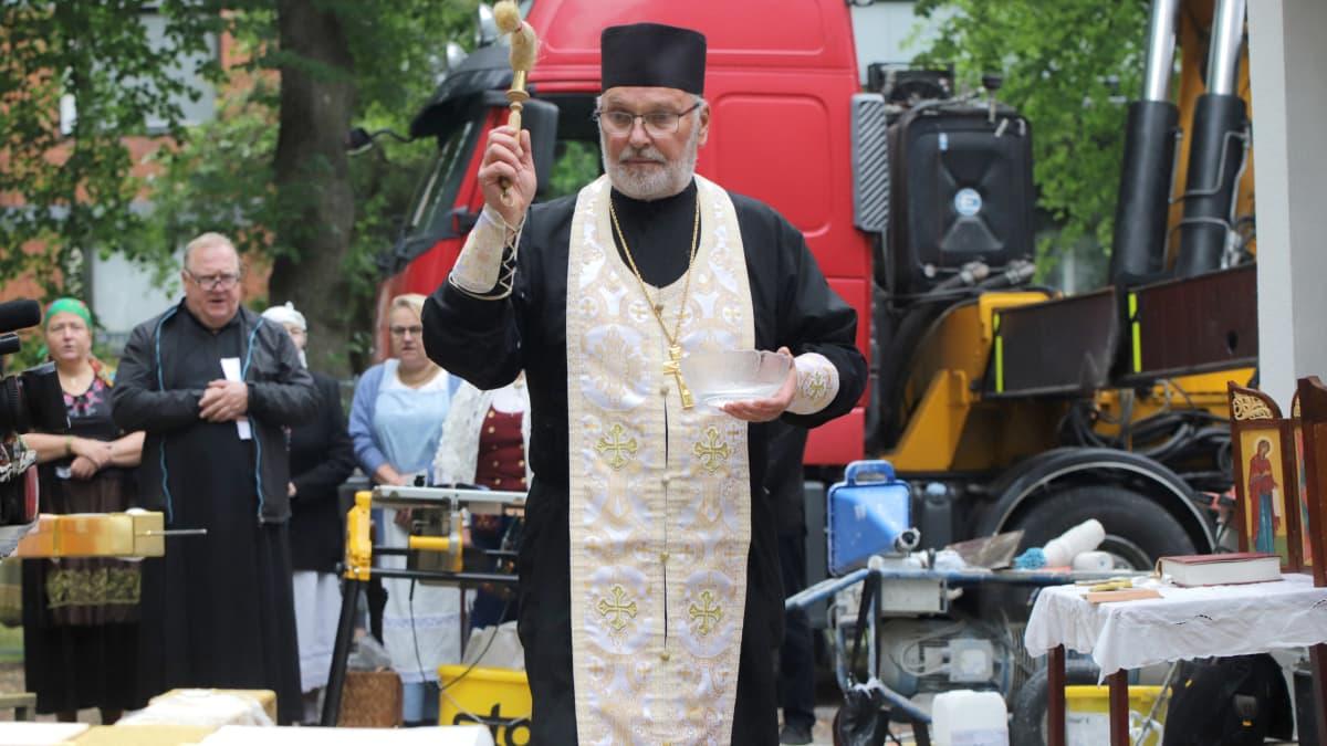 Ortodoksipappi siunaa ulkona remonttityömaan keskellä kirkon katolle nostettavaa ristiä.
