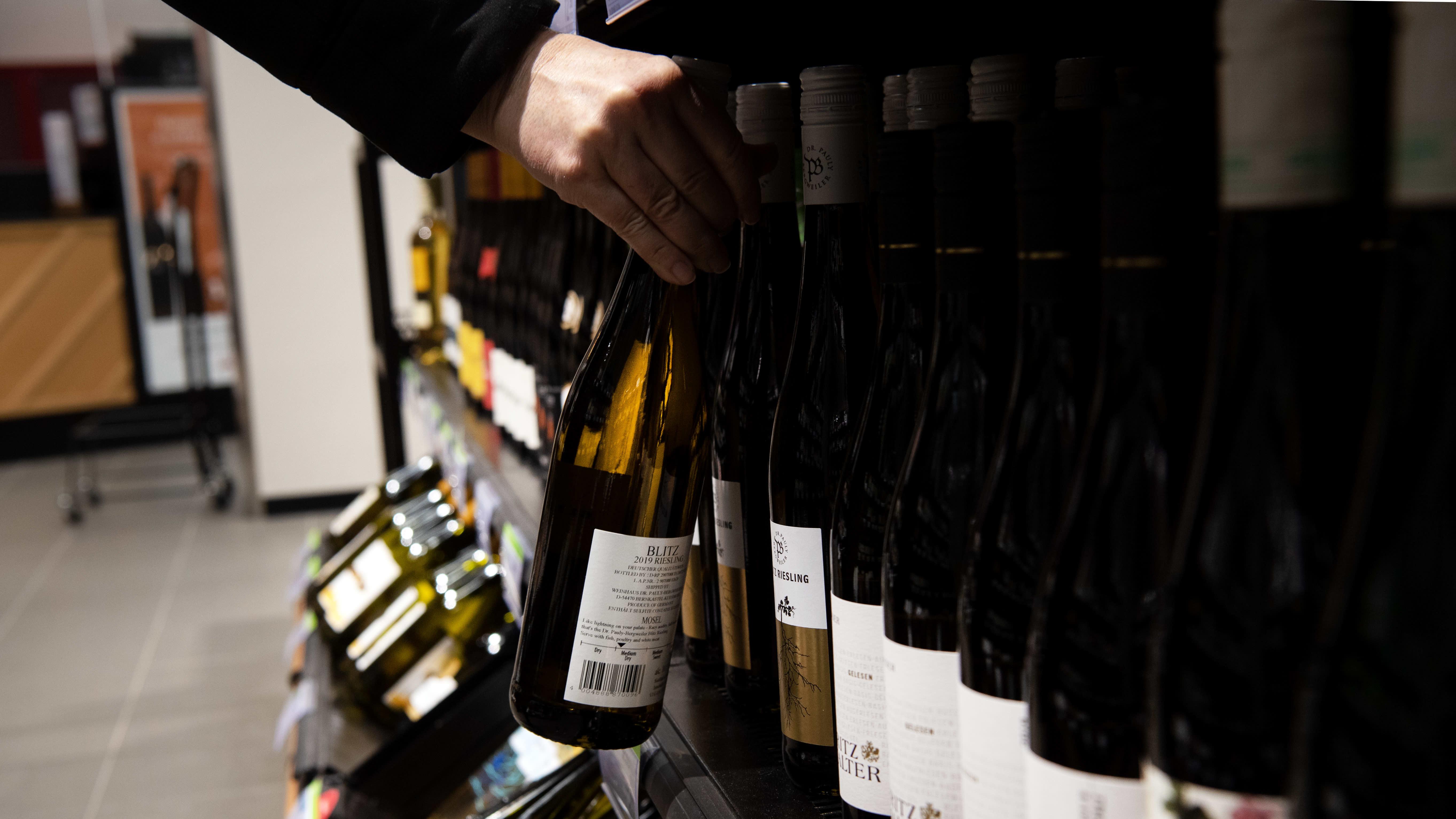 Asiakas viinihyllyn luona Alkossa.