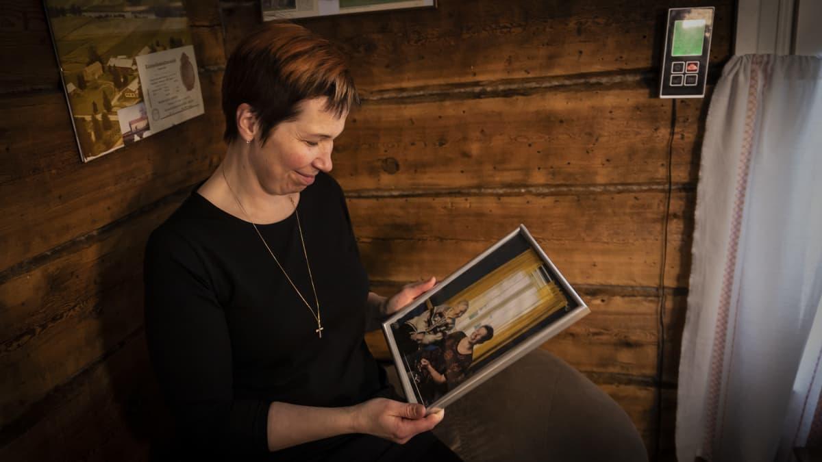 Nainen pitelee kädessään kuvaa, jossa hän hymyilee isoäitinsä kanssa.