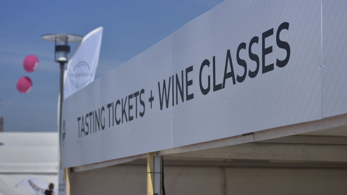 en skylt med texten tasting tickets and wine glasses på ett festivalområde