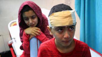 Kaksi lasta istumassa sairaalasängyllä. Toisen päässä on kääre.
