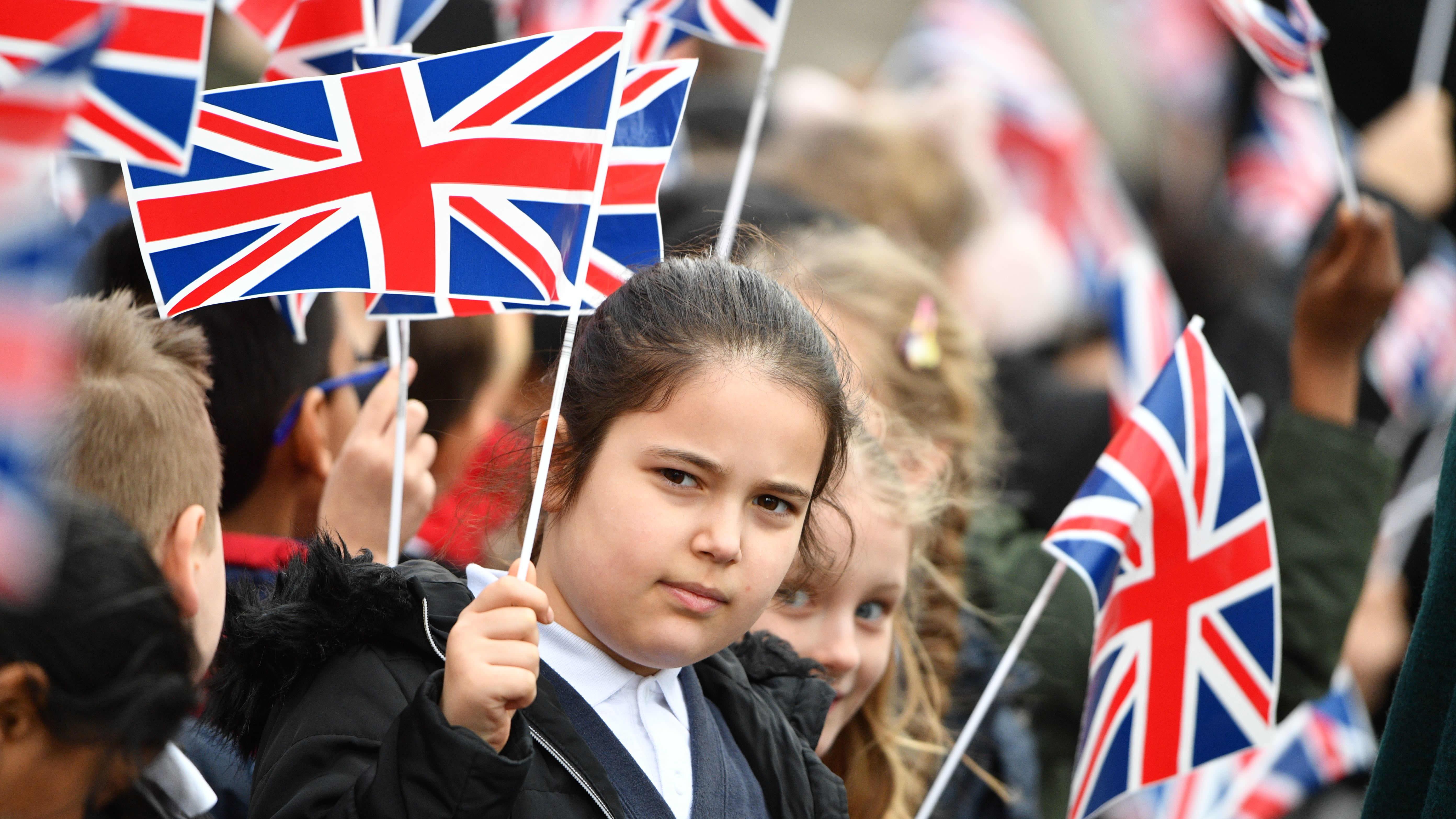 Koululaiset heiluttavat pieniä Britannian lippuja.