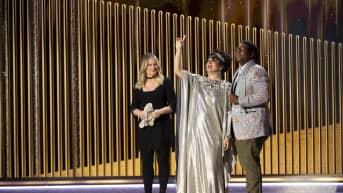 Amy Poehler, Maya Rudolph ja Kenan Thompson seisovat lavalla.