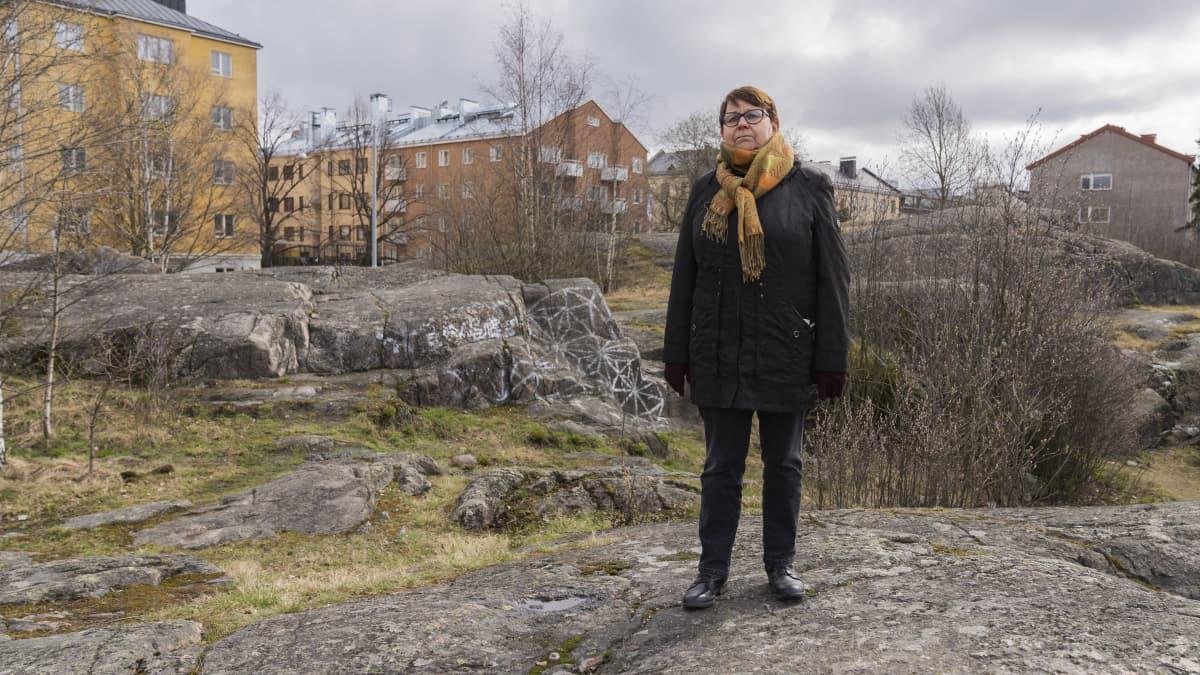 Alppila seuran puheenjohtaja Irja Nykänen kallioiden päällä Saimaanpuistikkossa.