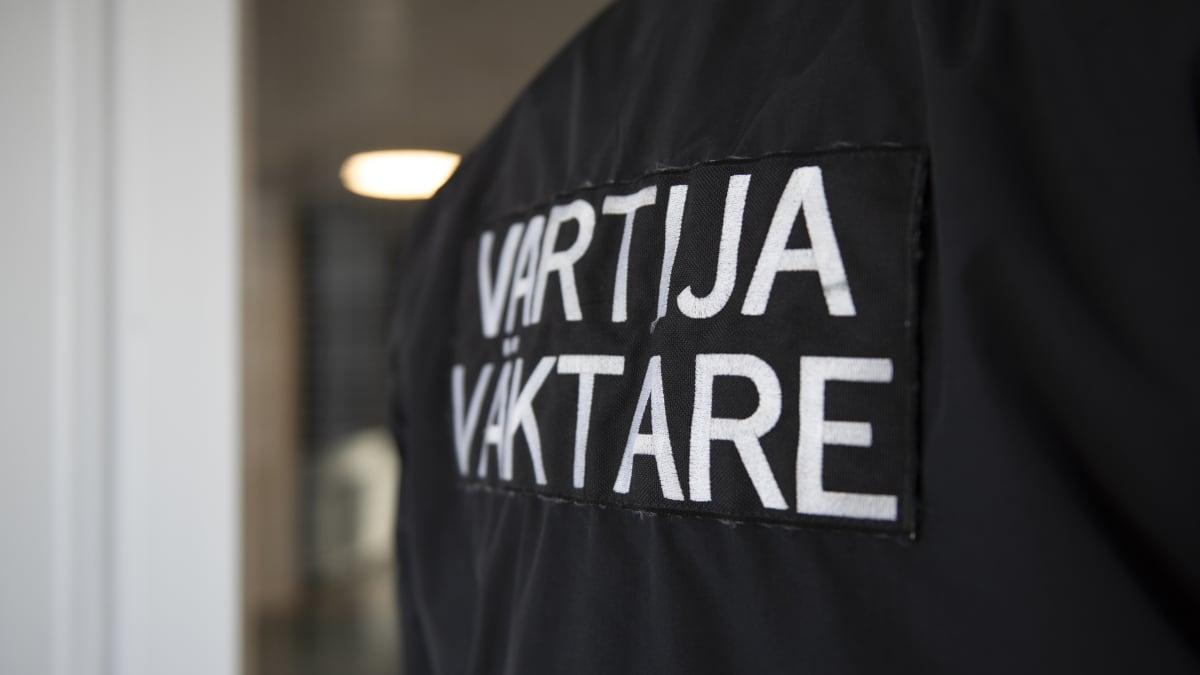 Vartijan selkä, jossa lukee suomeksi ja ruotsiksi vartija/väktare.