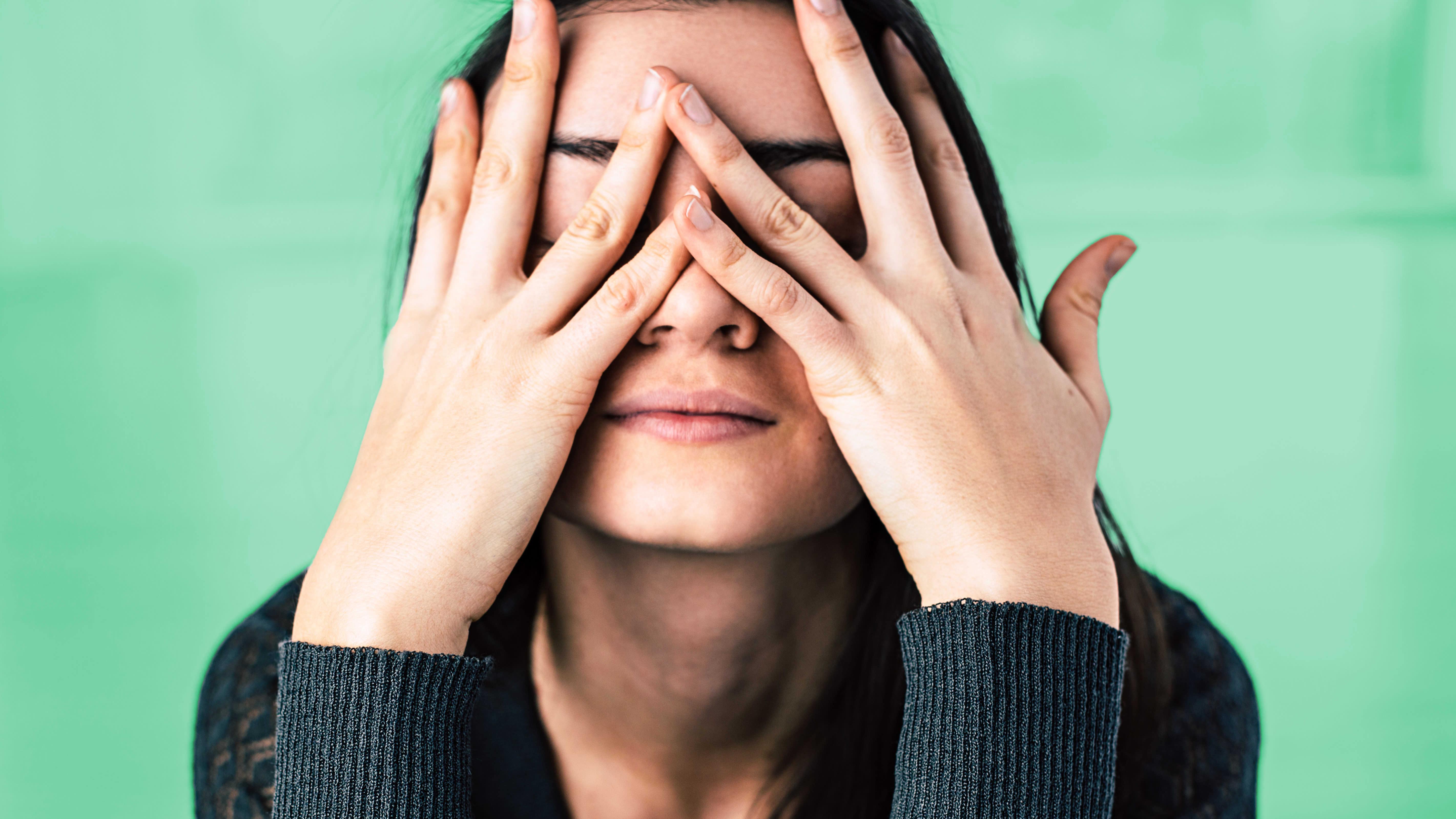 Epätoivoinen nainen pitää käsiä kasvoillaan