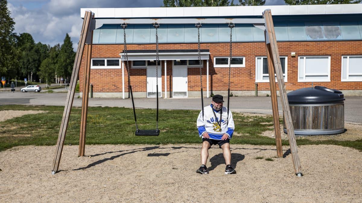 Ilkka Koskikara istuu keinussa vanhan koulunsa pihalla.