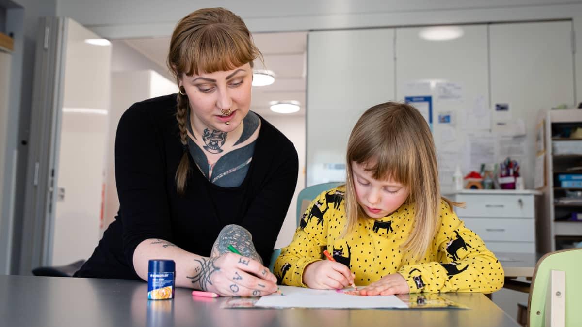 Kaisa Niskanen värittää paperia tyttärensä kanssa.