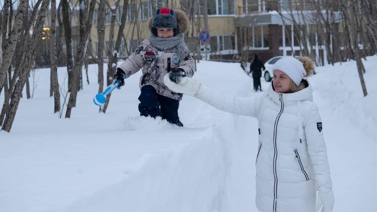 Pikkupoika kävelee lumihangella äidin pitäessä kiinni kädestä.