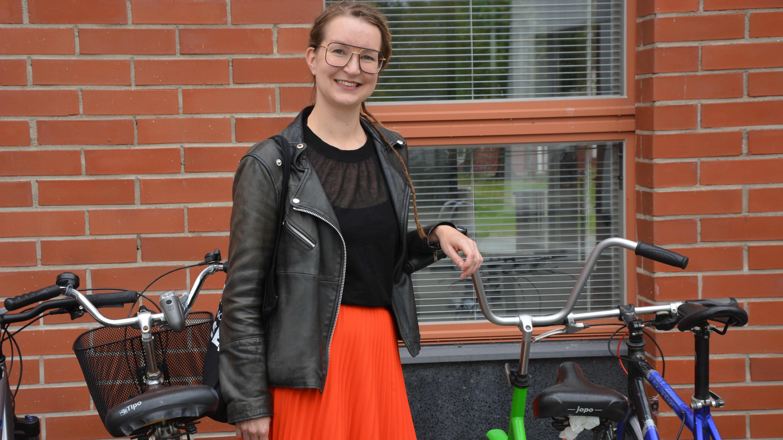 Ung kvinna vid cykelställning.