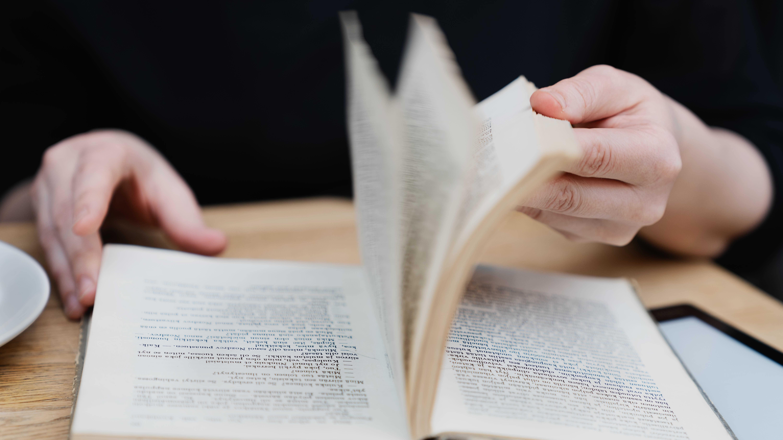 Väitöskirjatutkija Anna Kajander selailee lempikirjansa sivuja, joille joku on aikanaan piirrellyt.