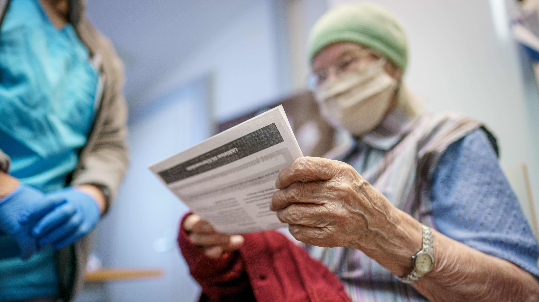 Eeva Nikander lukee ohjetta koronan tehosterokotuksesta saatuaan juuri ensimmäisen rokotuksen.