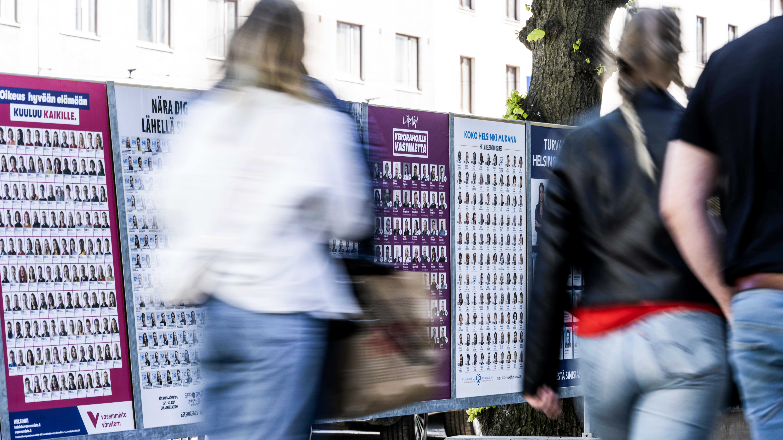 Ihmisiä kävelee kuntavaalimainosten ohi Töölönkadulla Helsingissä.
