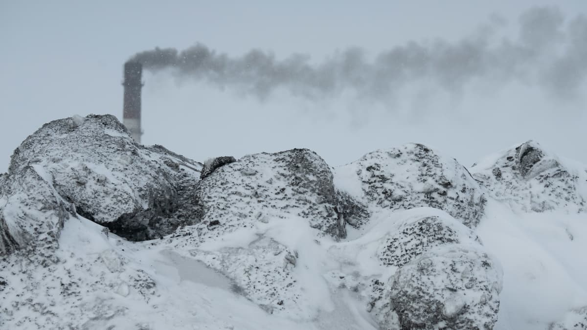 Harmaaksi värjäytynyttä lunta ja savupiippu.