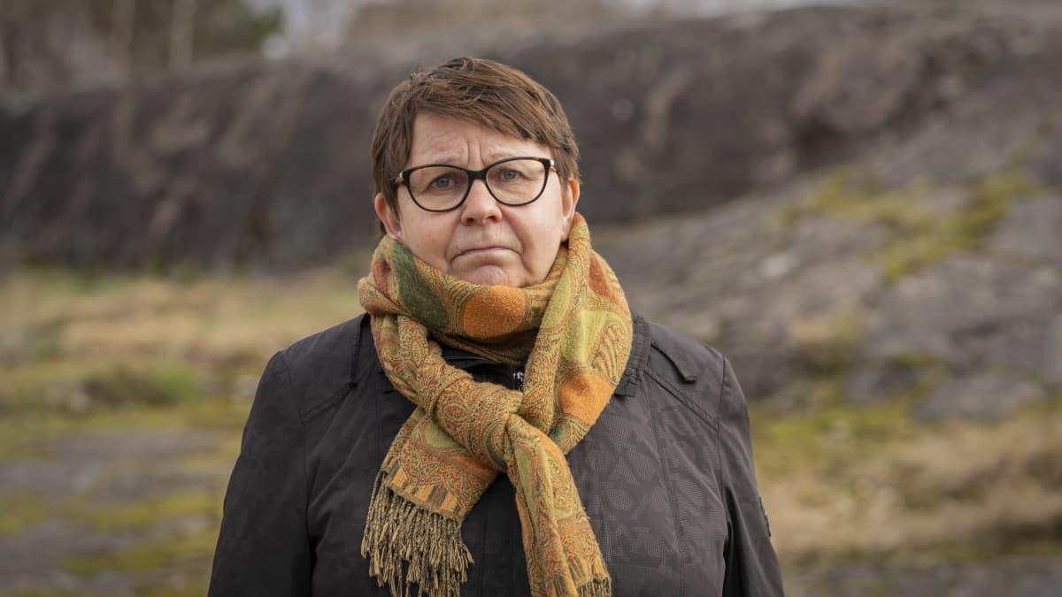 Alppila seuran puheenjohtaja Irja Nykänen kuvattuna kallioita vasten.