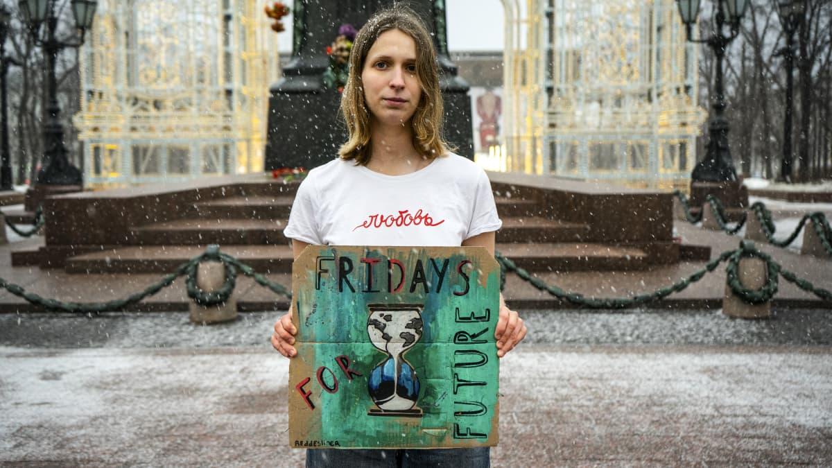 Nainen Fridays for Future -kyltti käsissään.
