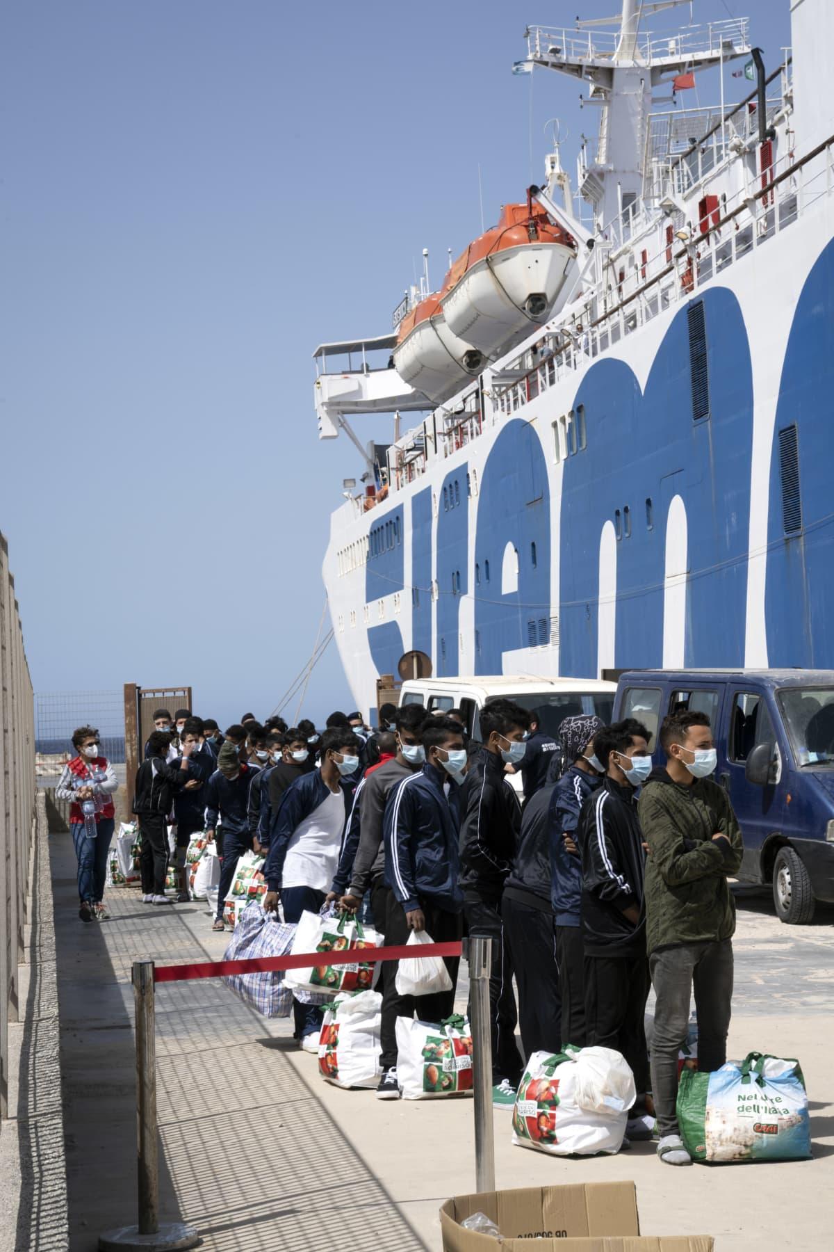 Siirtolaisi jonossa satamassa Lampedusassa.