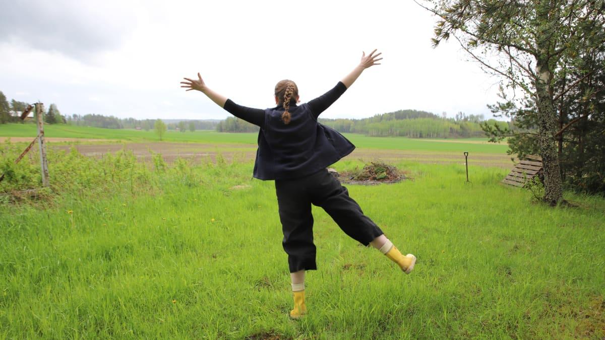 Nainen maalaismaisemassa hypähtämässä ilmaan