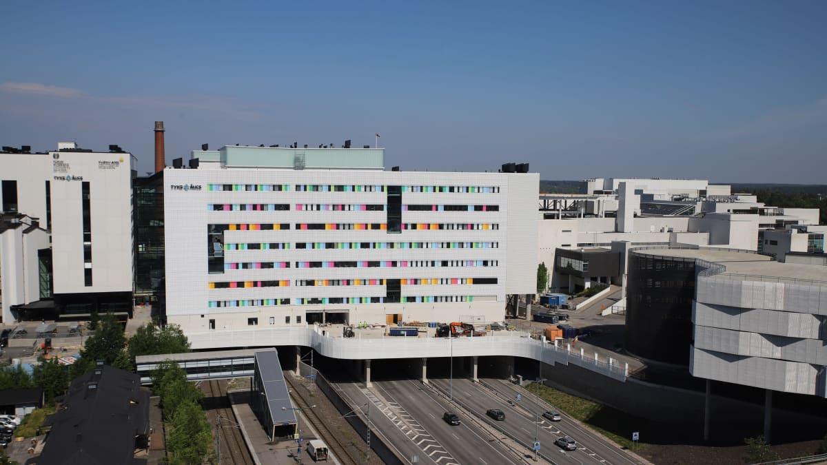 Valkoinen sairaalarakennus moottoritien päällä, värikkäitä yksityiskohtia ikkunoiden vieressä