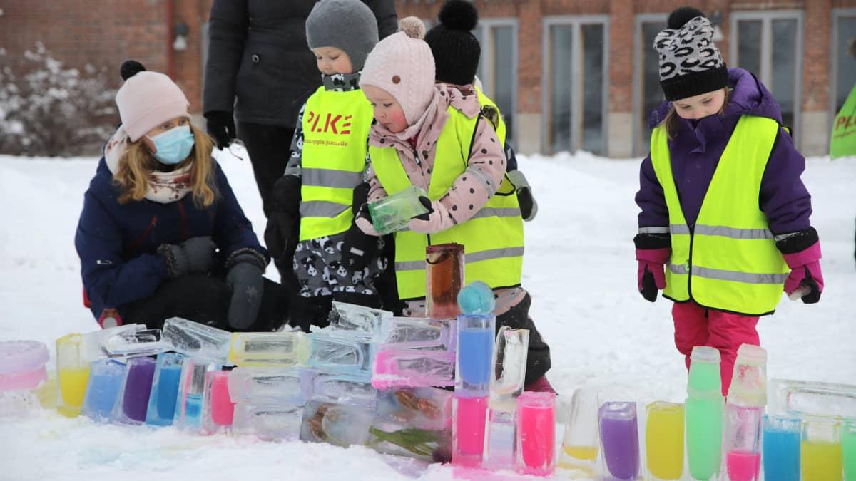 Lapset rakentavat jääpalikoista taideteosta talvisella pihalla