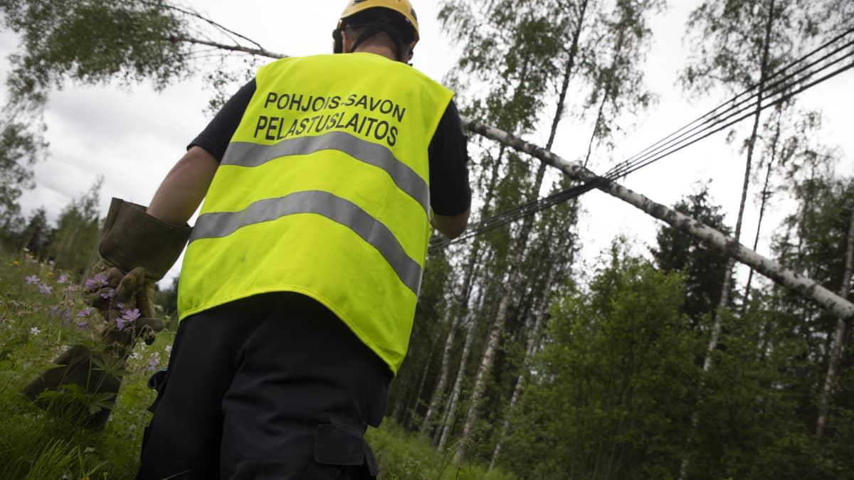 Pelastuslaitoksen työntekijä ja linjoille kaatunut puu