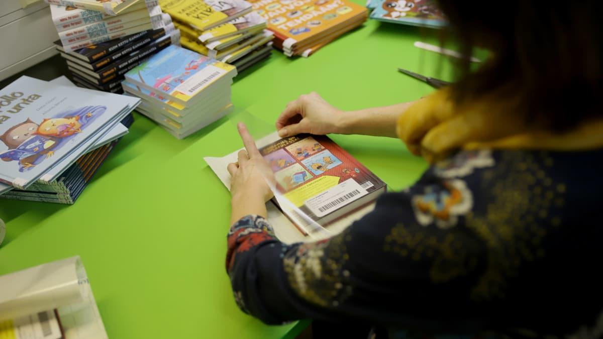 nainen päällystää kirjoja kontaktimuovilla