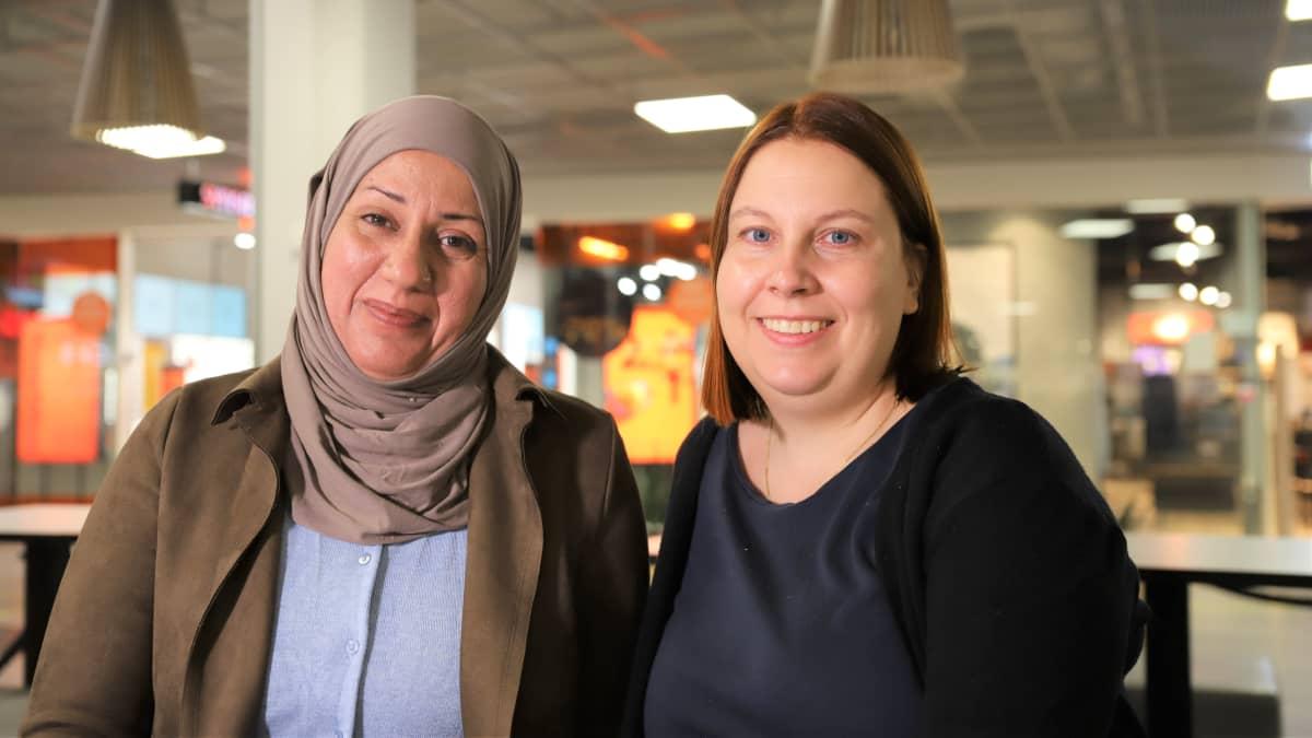 Irakista Suomeen tullut Roqaya Al-Anbagi ja suomalainen Paula Malan hymyilevät kameralle Trion kauppakeskuksessa Lahdessa.