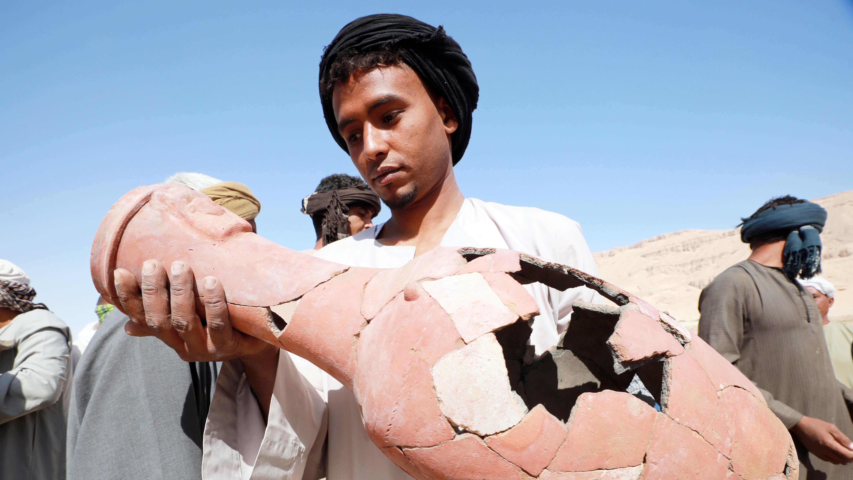 Työntekijä katsoo arkeologiselta kaivaukselta löytynyt ruukkua.