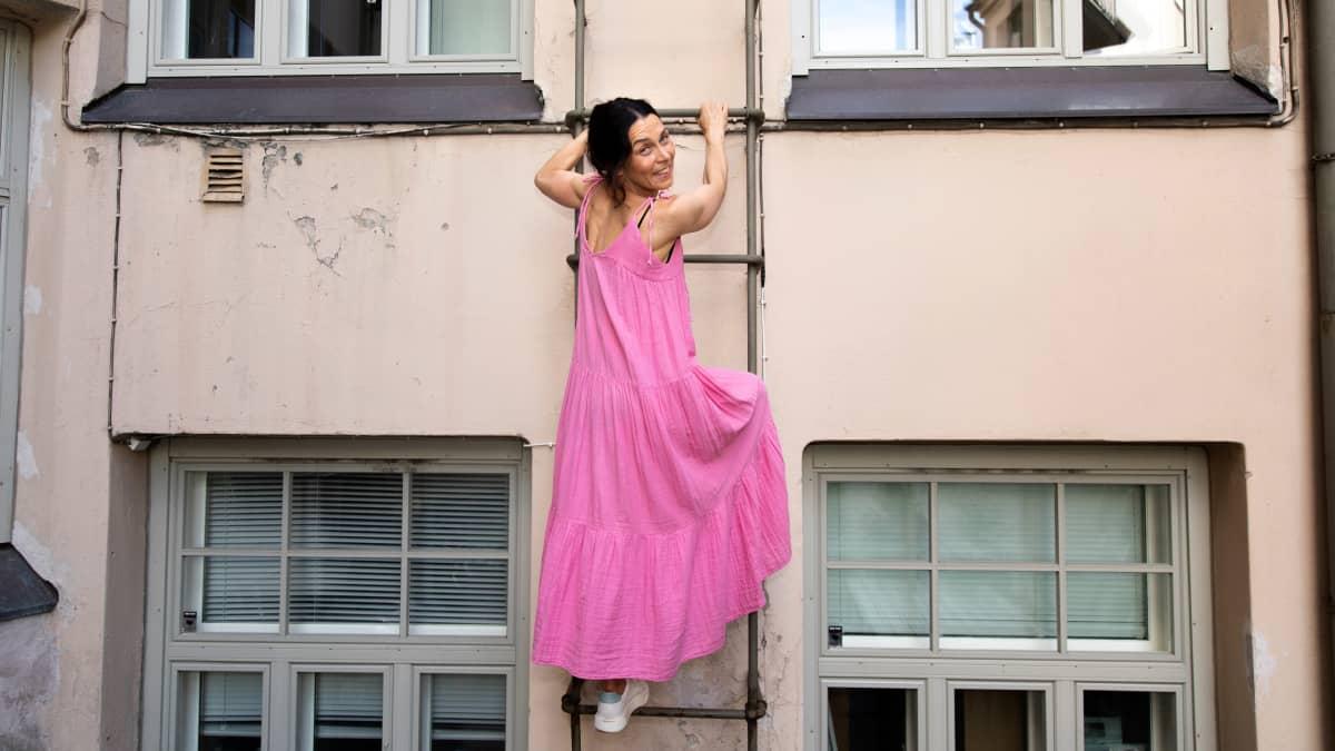 Nainen vaaleanpunaisessa kesämekossa kiipeää tikapuita ylös ja hymyilee. Takana kerrostalon seinä ja ikkunoita.